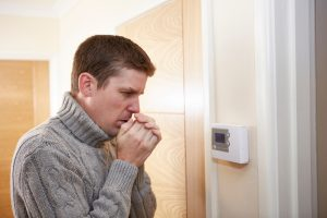 man looking very cold standing in front of thermostat
