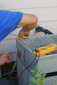male technician working on outside unit of an air conditioner
