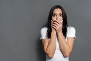 woman looking very concerned with hand over mouth